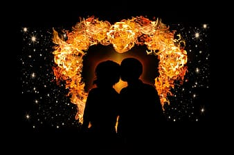 Silhouette of two person with flame as back drop