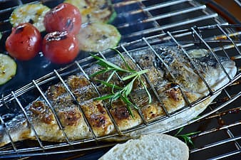 Grilled fish and tomatoes on top of grill