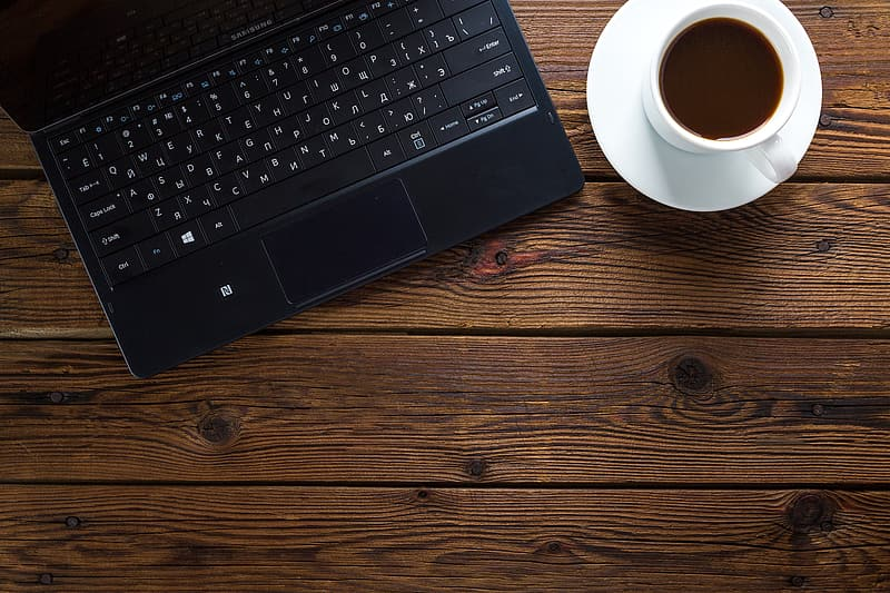 Black laptop computer beside white ceramic teacup with saucer on brown wooden surface