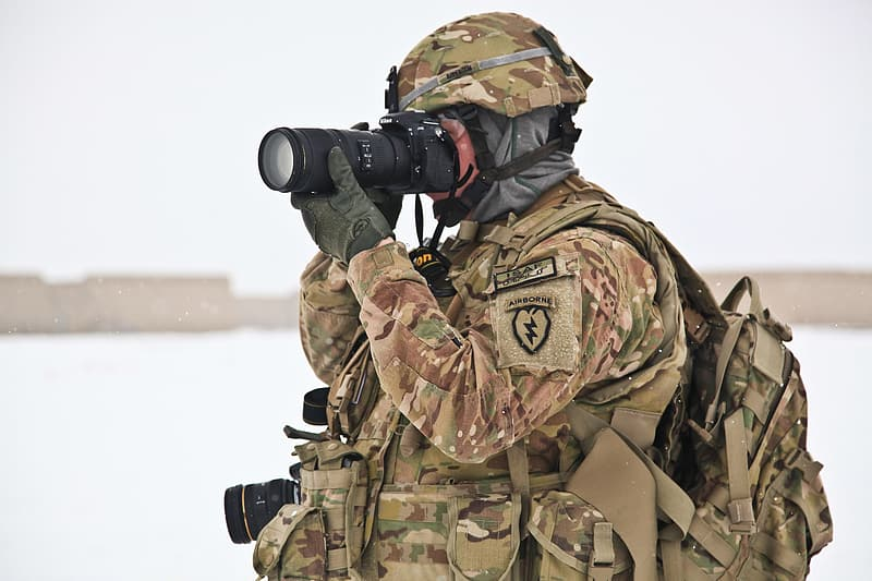 Soldier wearing brown and green camouflage uniform looking through DSLR camera