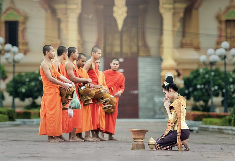 Woman kneeling in front of brass-colored container