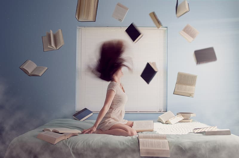 Photo of woman in bed with flying books