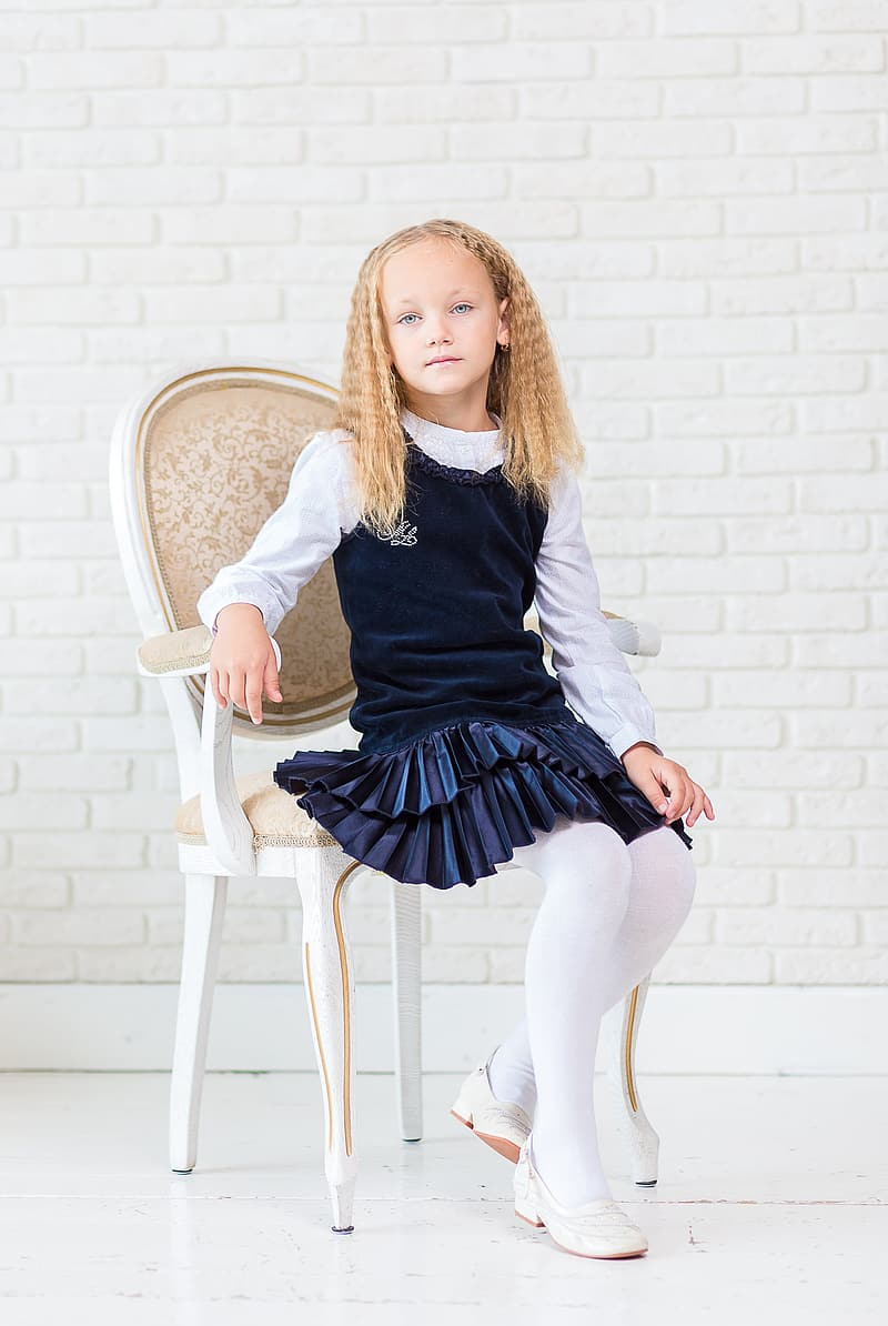 Yellow haired girl in blue and white dress sitting on chair