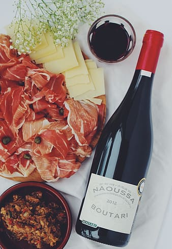 Photo of Naoussa Boutari bottle beside bowl and raw meat