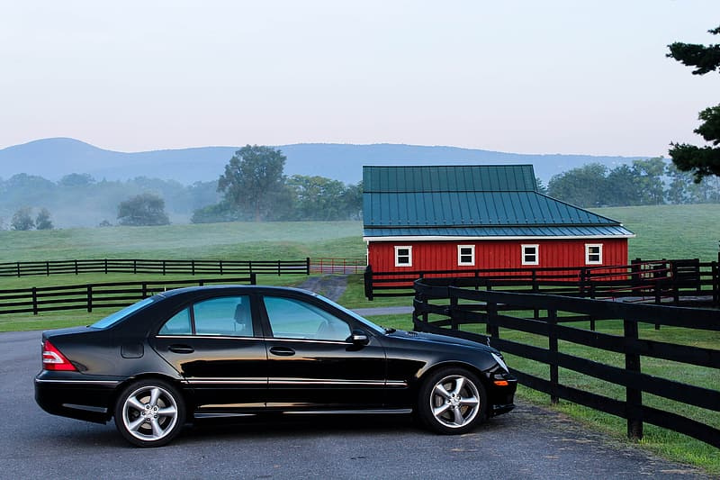 Black sedan parked on concrete ground near red and black barn house