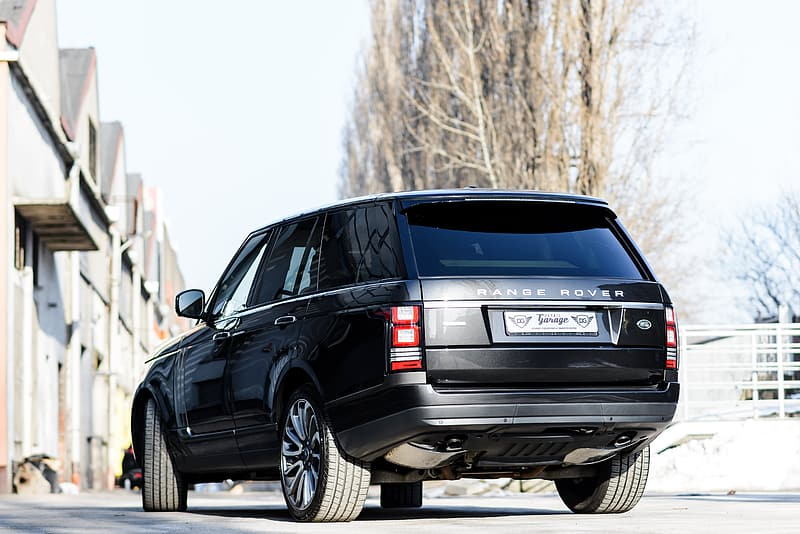 Black Land Rover Range Rover SUV making a turn during daytime