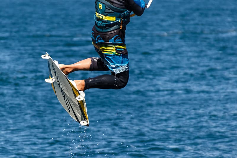 Person riding wakeboard on body of water