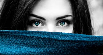 Selective color photography of woman showing blue eyes and blue textile