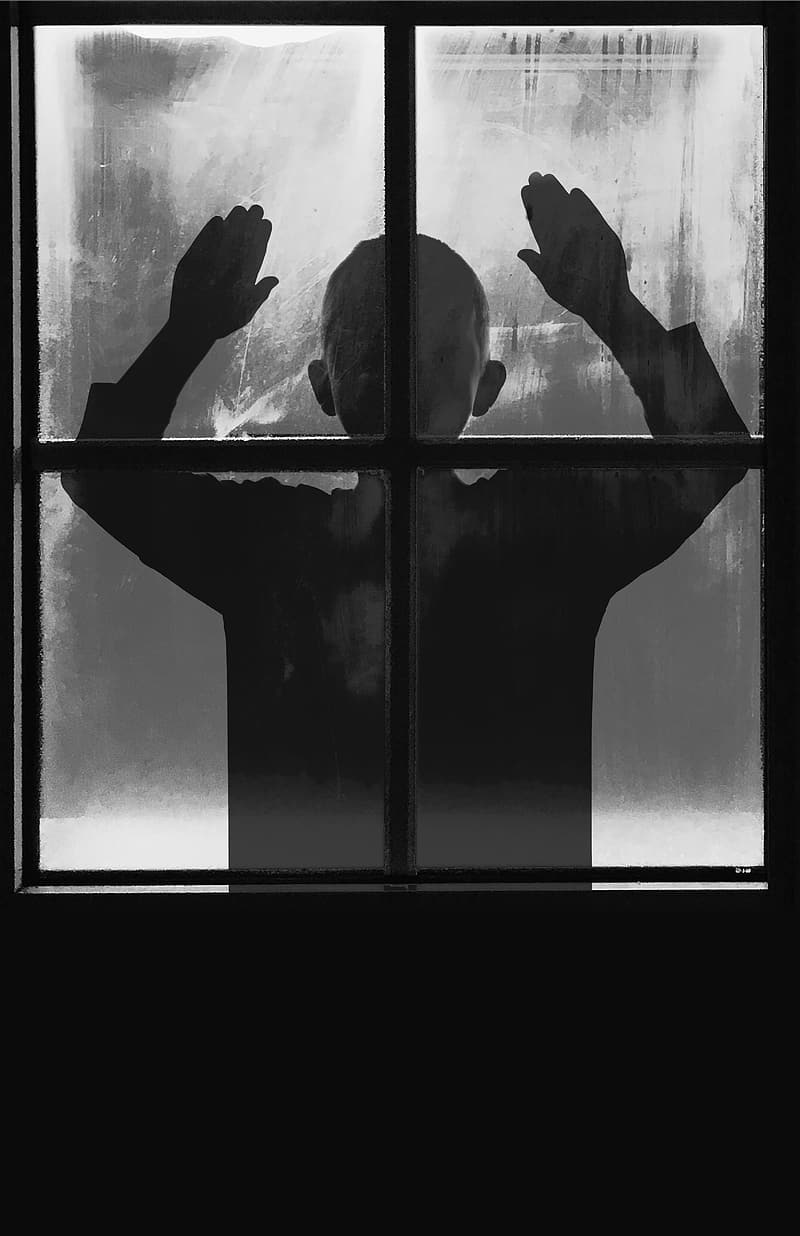 Silhouette of toddler standing in front of window