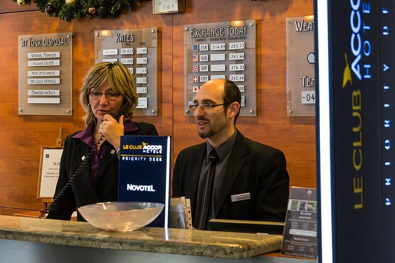 Man and woman standing in front of LE Club front desk