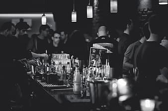 Grayscale photo of group of people at the bar