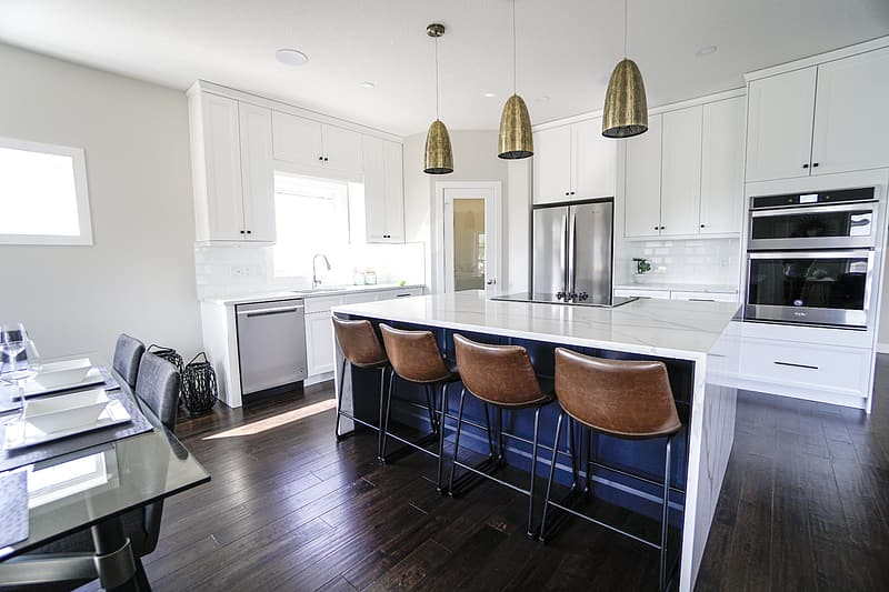 Brown and gray chair near white wooden kitchen cabinet
