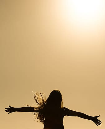 Silhouette of woman spreading her hands photo