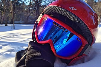 Closeup photo of helmet with goggles on snow