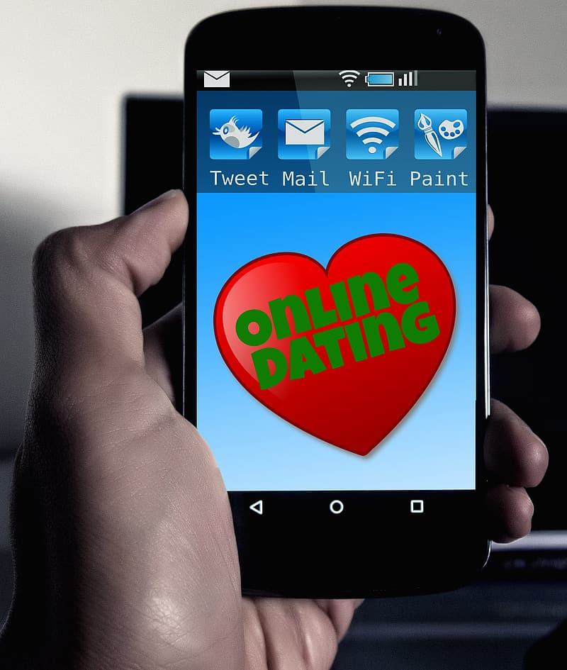 Person holding phone displaying online dating template