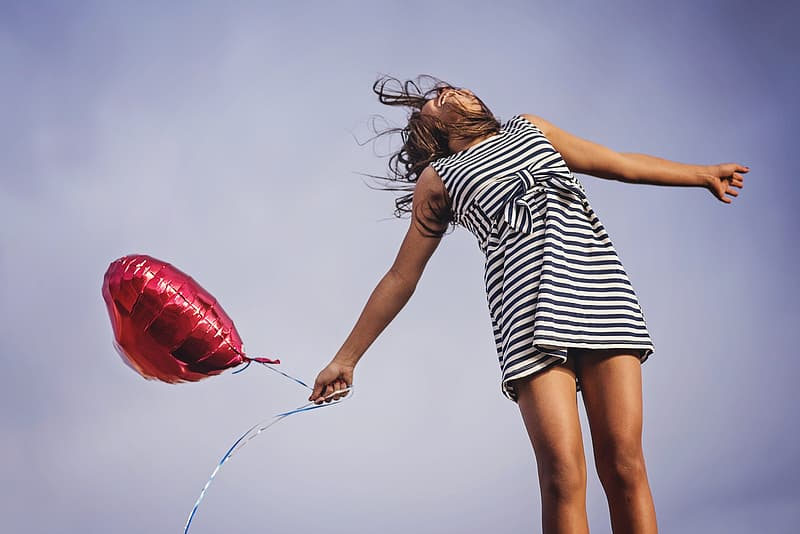 Photo of woman holding red heart balloon