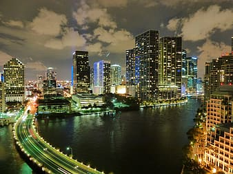 Concrete bridge surrounded high-rise buildings at nighttime