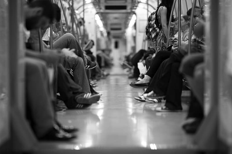 Grayscale photography of people sitting in train