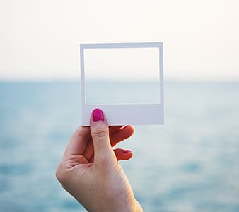 Person's hand holding white square paper frame