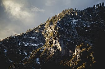 Mountain covered with trees and snow under cloudy sky during daytime