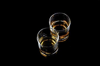 Two clear glass cups with brown liquid