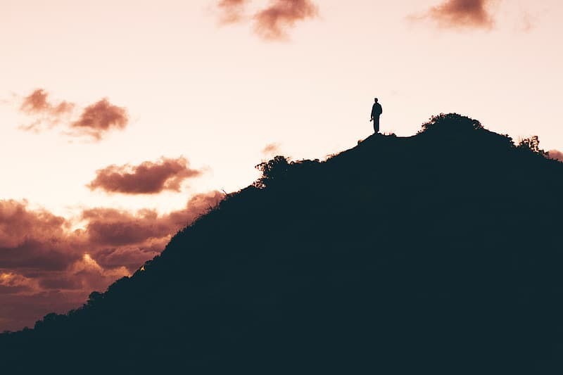 Silhouette of person standing on top of hill