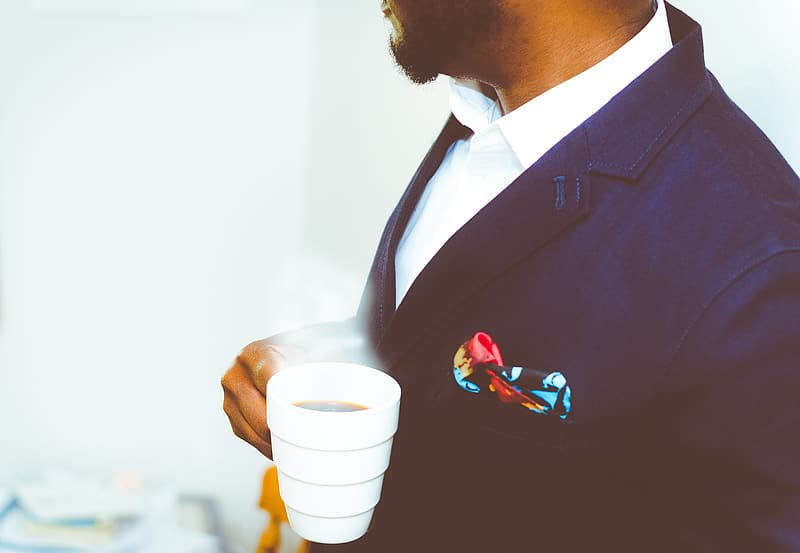 Man in black suit holding white disposable cup