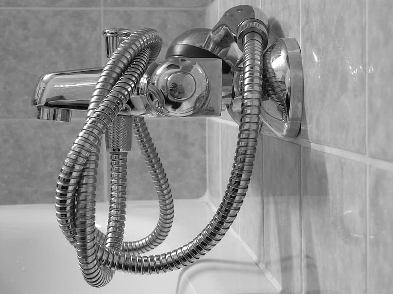 Selective focus photo of faucet with hose