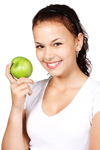 Woman in white shirt holding green apple