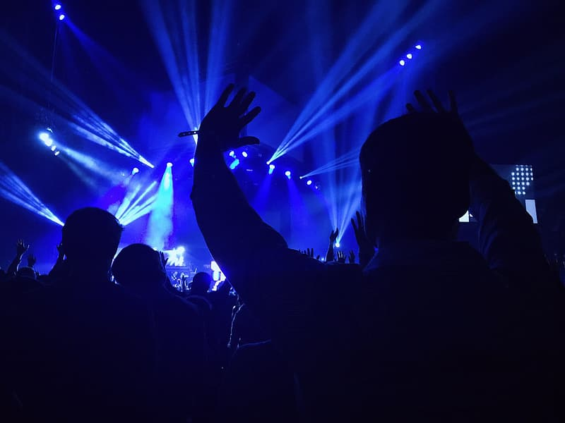 Silhouette of people near blue stage lights