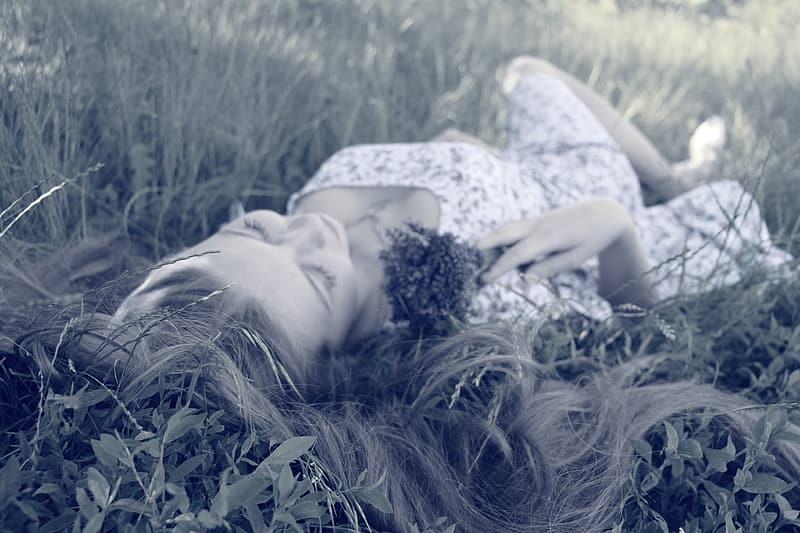 Woman in white dress lying on grass