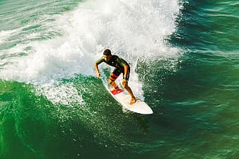 Male surfer on white surfboard riding on tidal wave