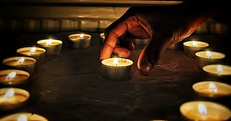 Person holding lighted candle on brown wooden table