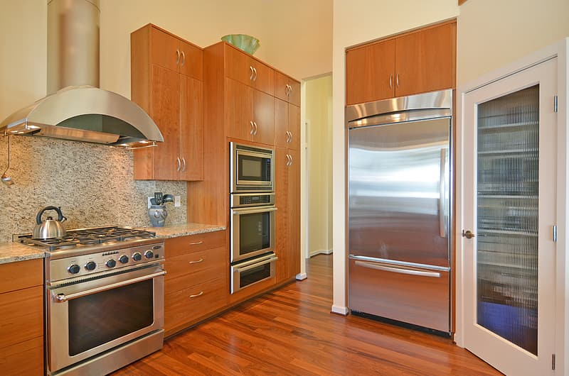 Silver gas range oven and brown wooden kitchen cabinets