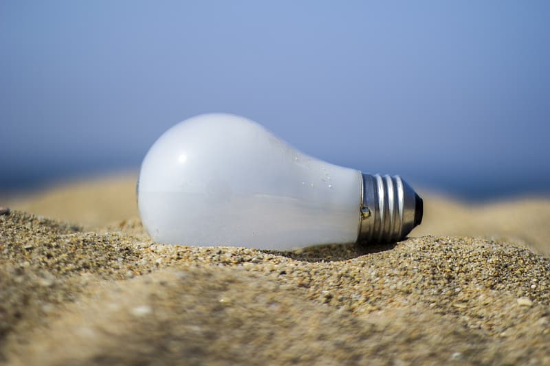 Close-up photography of white bulb on brown sand