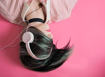 Woman in white and pink striped shirt wearing white headphones