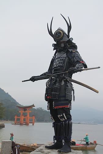 Samurai on gray concrete near body of water during daytime