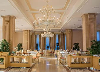 Empty chairs and table arrangement and uplight chandelier building interior