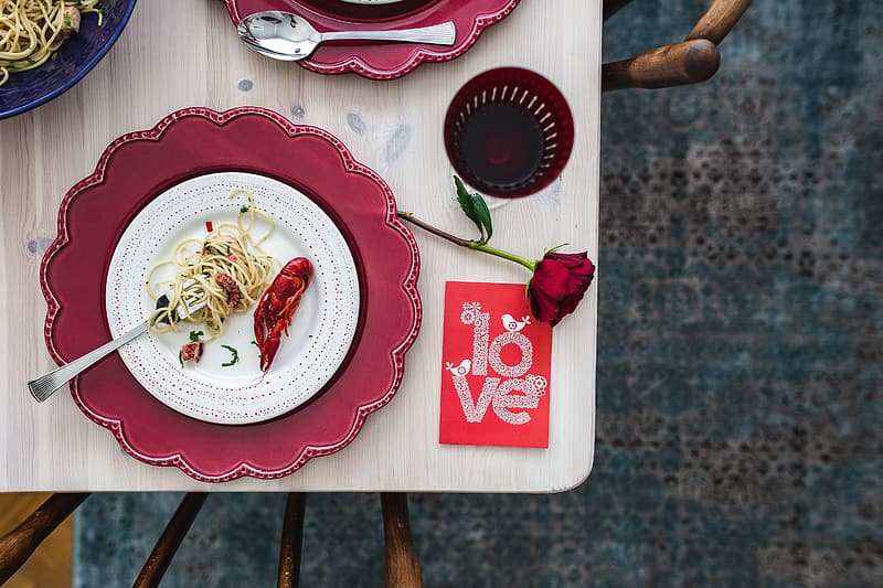 White and red ceramic plate with food on brown wooden table