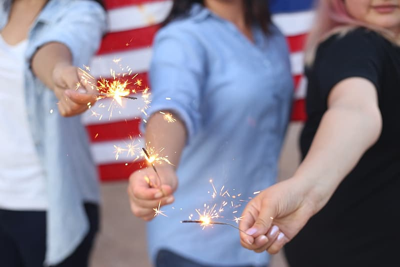 Three person holds lighted sparkler firecrackers
