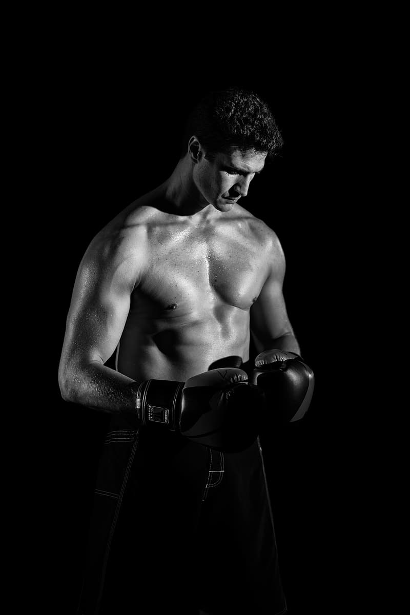 Grayscale photo of man wearing boxing gloves