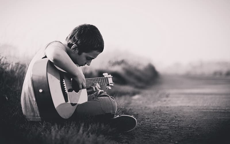 Grayscale photography of boy playing guitar