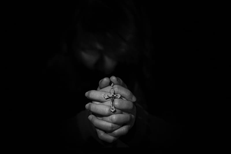 Closeup grayscale photography of person's hand holding rosary