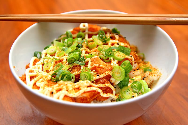 Green onion and pasta dish on white ceramic bowl and brown chopstick on top