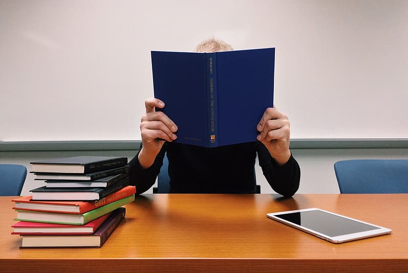 Person holding blue book leaning on brown wooden desk