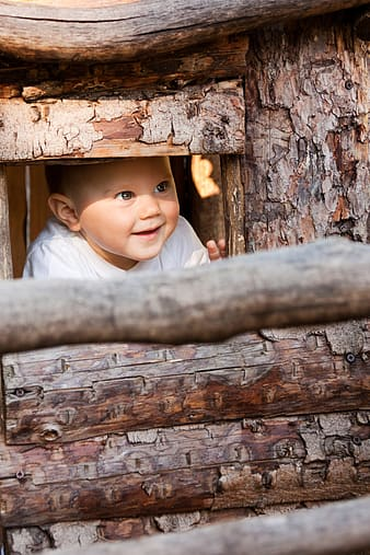 Baby in whit v-neck shirt peeping through brown wooden windpw