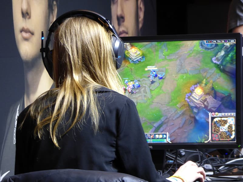 Woman wearing black long sleeve top in front of computer monitor playing League of Legends | Pikrepo