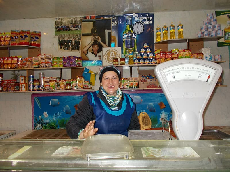 Woman in blue long sleeve shirt standing beside food stall