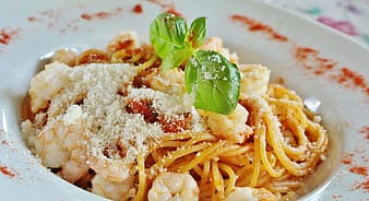 Pasta with green leaf on white ceramic plate