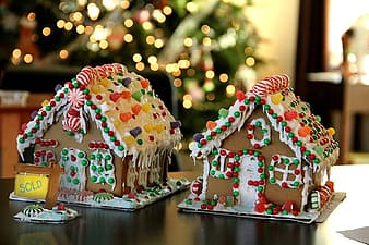 Two ginger bread houses on brown tables